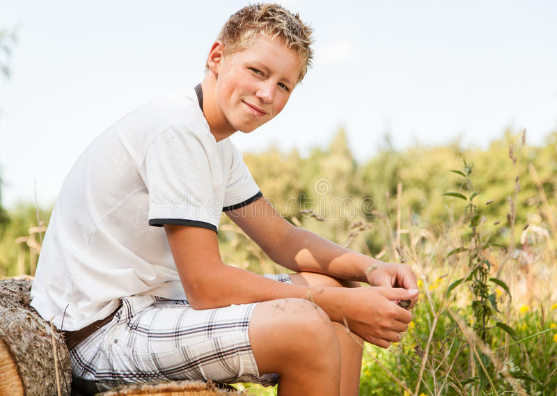 Handsome friendly young boy sitting outdoors. Handsome friendly young teenage boy sitting outdoors on a pile of logs in the countryside turning to smile at the stock photography