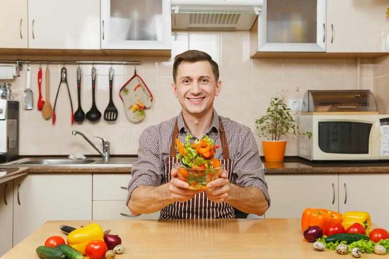 Handsome caucasian young man, sitting at table. Healthy lifestyle. Cooking at home. Prepare food. Handsome fun caucasian young man in apron, brown shirt sitting royalty free stock photo