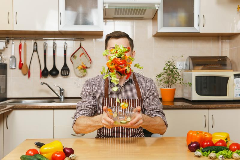 Handsome caucasian young man, sitting at table. Healthy lifestyle. Cooking at home. Prepare food. Handsome fun caucasian young man in apron, brown shirt sitting stock image