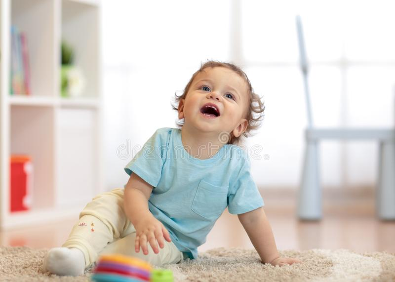 Handsome funny curly little boy sits on soft carpet in room and looks up. Handsome funny curly little baby boy sits on soft carpet in room and looks up royalty free stock photos