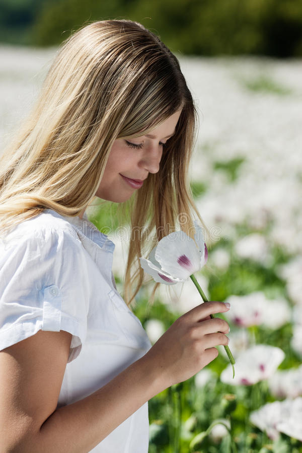 Handsome girl smells poppies royalty free stock image
