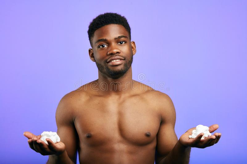 Handsome man holding shaving foam,preparing for shave, isolated in the blue background stock photos