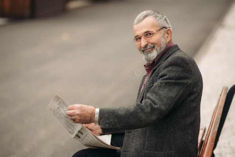 Handsome grandfather with a beautiful beard in a gray jacket sits on a bench in the park and reads a newspaper stock photo