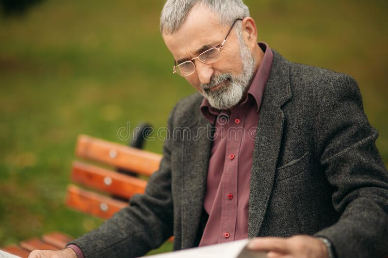 Handsome grandfather with a beautiful beard in a gray jacket sits on a bench in the park and reads a newspaper stock images