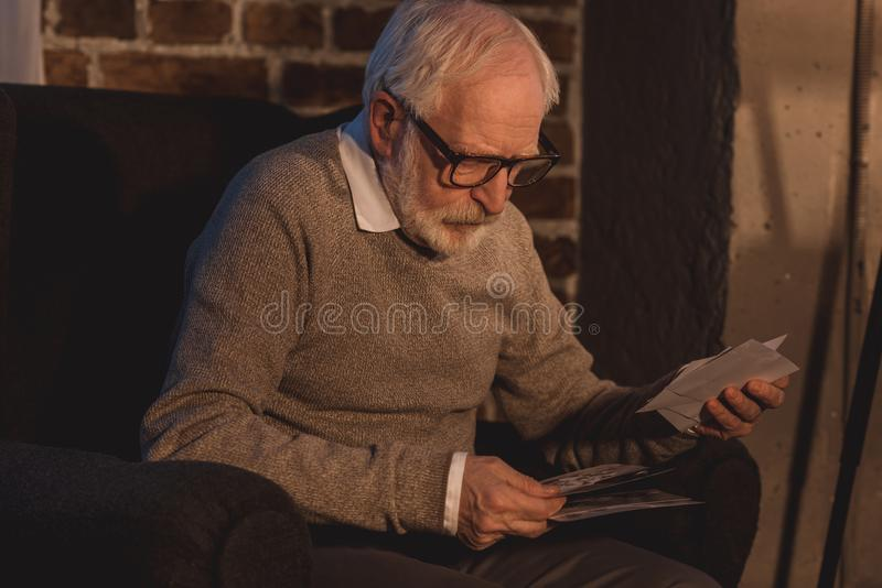 handsome grey hair man sitting in armchair and looking at old photos royalty free stock photos
