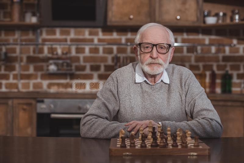 handsome grey hair man sitting at table with chessboard and looking royalty free stock image