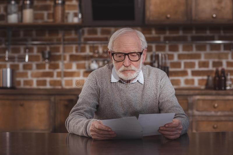 handsome grey hair man sitting at table and looking at photos royalty free stock images