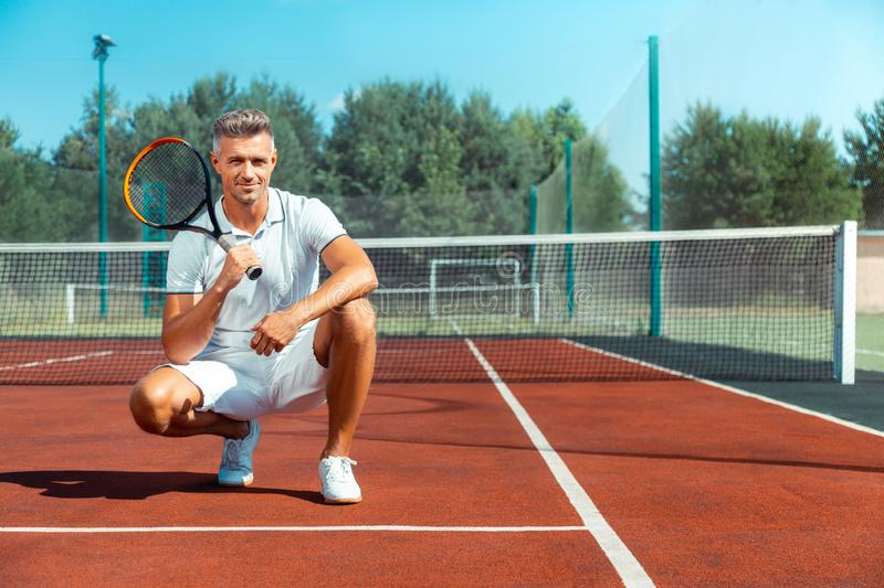 Handsome grey-haired businessman holding tennis racket stock photo