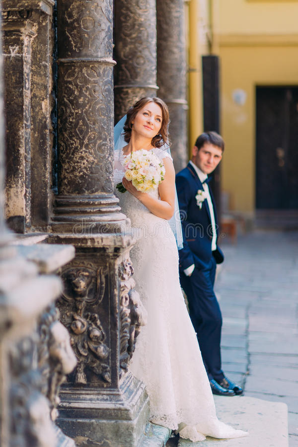 Handsome groom on background, the bride standing between columns of old building holding bridal bouquet stock photos
