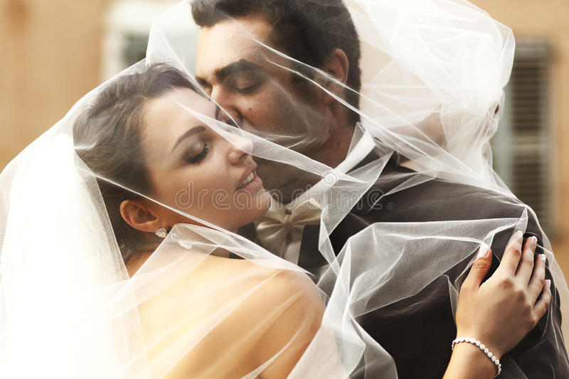 Handsome groom and beautiful bride kissing under veil in old street closeup stock images