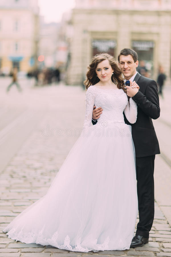 Handsome groom in black suit holds the hand of bride wearing white dress, old sunny city background stock image
