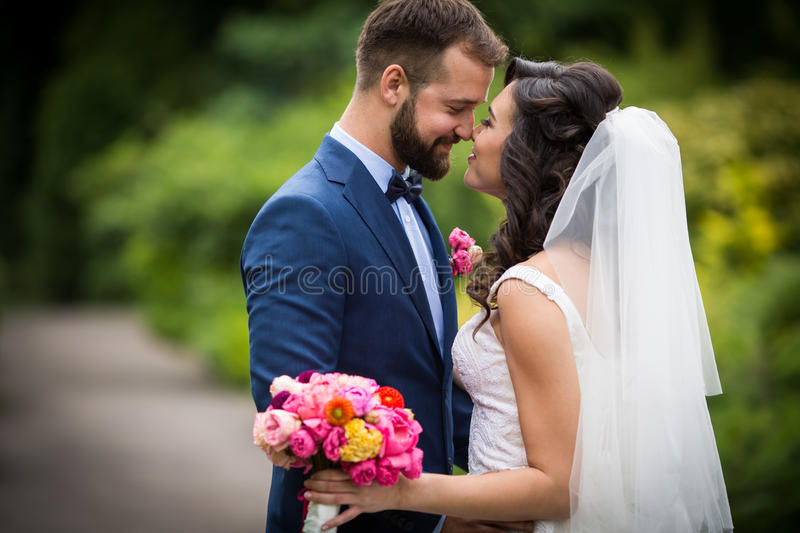 Handsome groom hugging beautiful bride with bouquet in romantic stock images