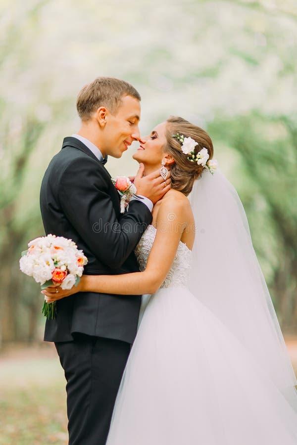 Handsome groom hugging beautiful bride with bouquet in romantic european park stock photo