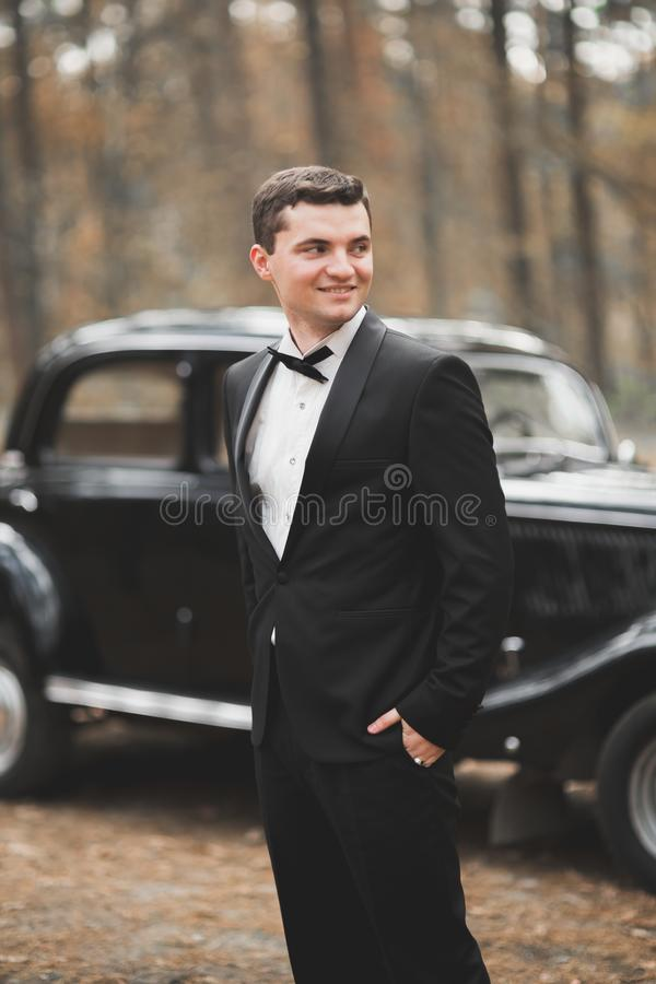 Handsome groom at wedding smiling and waiting for bride near retro car.  royalty free stock photography
