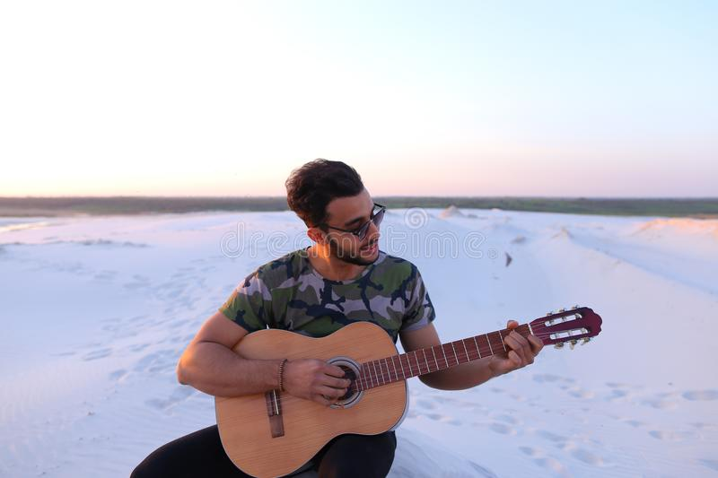 Cute young male Arab enjoys sound of guitar, sitting on hill in stock images