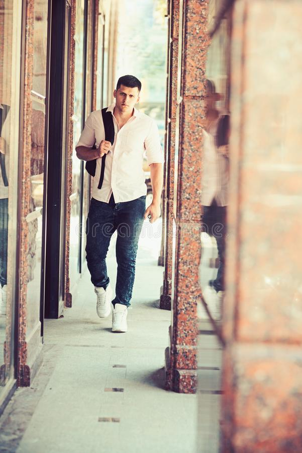 Handsome guy with backpack on vacation. Man with travel bag on sunny outdoor, wanderlust. Macho in fashionable shirt and. Jeans. Fashion model on street. Youth royalty free stock photos