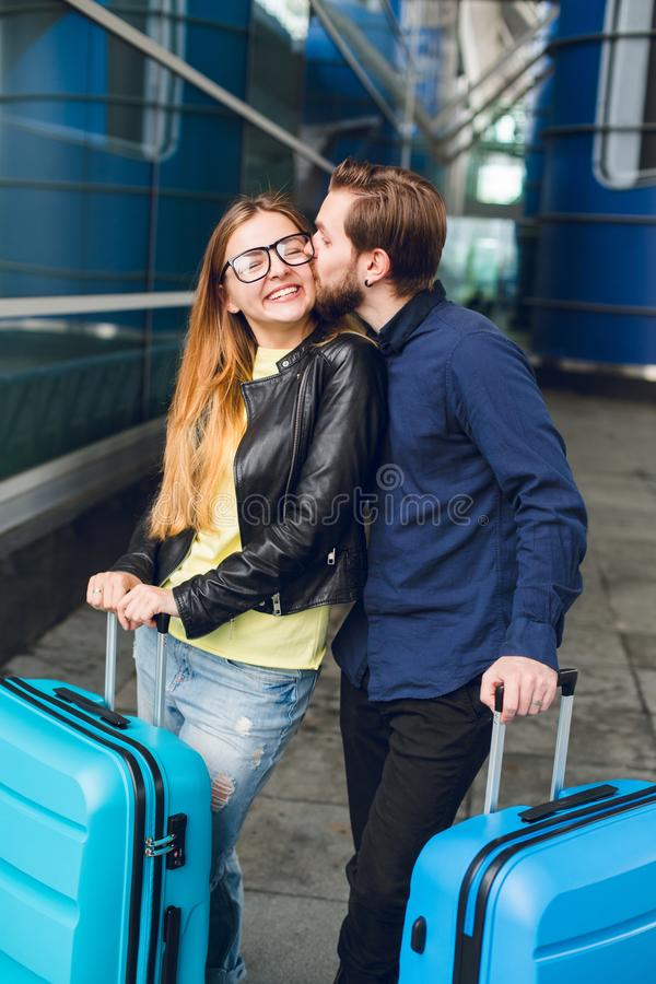 Handsome guy with beard in black shirt is kissing girl with long hair outside in airport. She wears glasses, yellow.  royalty free stock images