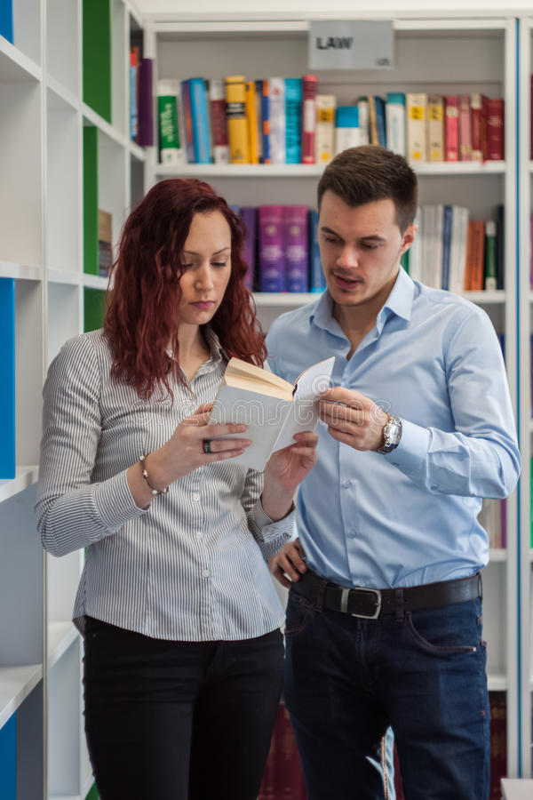 Handsome guy and beautiful redhead girl studying in the library stock image