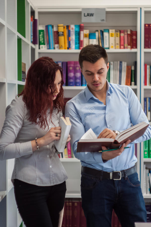 Handsome guy and beautiful redhead girl studying in the library royalty free stock images