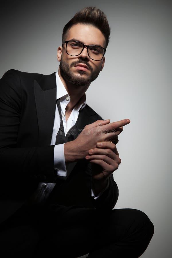 Handsome guy in black tuxedo rubbing hands stock photo