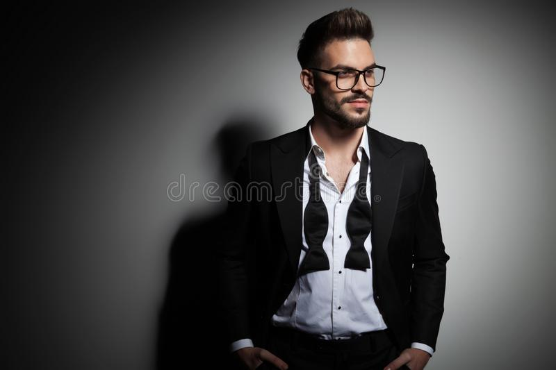 Handsome guy in black tuxedo with undone collar looking away royalty free stock photography