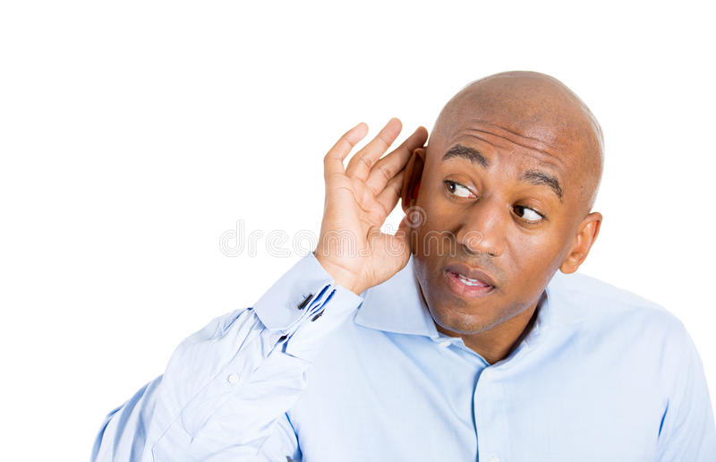 Handsome guy with blue shirt trying to secretly listen in on a conversation and shocked at what he hears royalty free stock image
