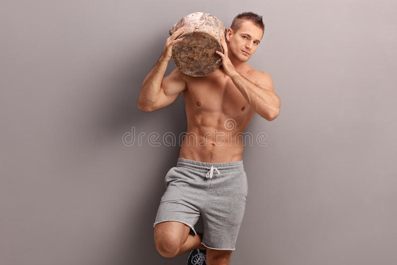 Handsome guy carrying a log on his shoulder. Handsome muscular guy carrying a huge log on his shoulder and looking at the camera stock images