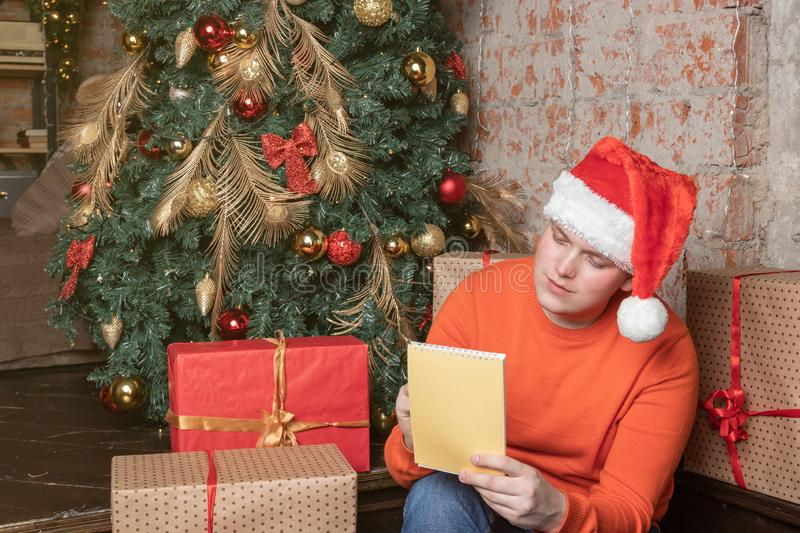 Handsome guy in christmas hat is writing a letter to Santa sitting under the tree surrounded by boxes of gifts. Christmas and stock images