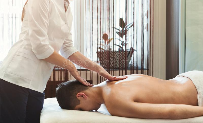 Handsome guy enjoying massage therapy. Handsome guy enjoying neck massage therapy in beauty center royalty free stock images
