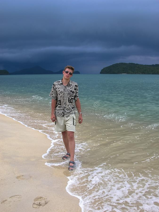 Handsome guy on an exotic beach. walk on the beach before tropical rain stock photography