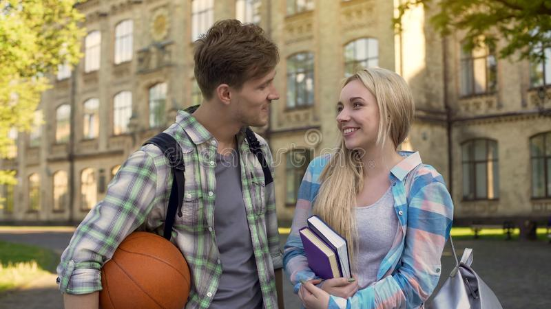 Handsome guy flirting with pretty female student, proposing girl to go to cinema. Stock photo stock photos