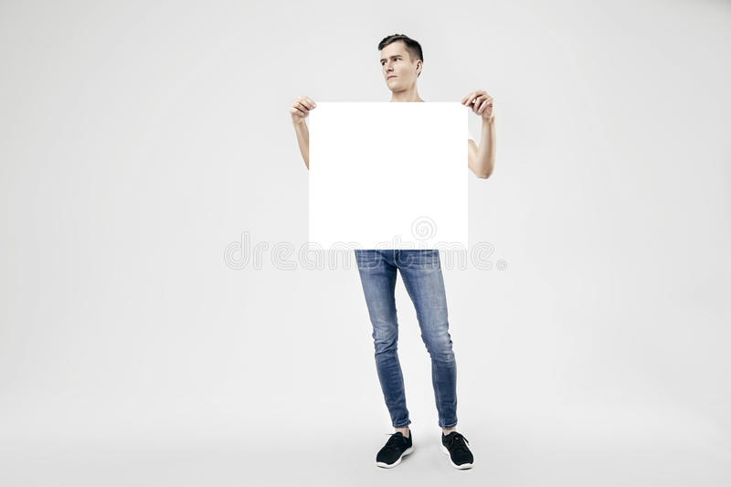 Handsome guy full-length standing with blank big poster or sheet in hands, isolated on white background. Wearing jeans and t-shirt stock photo