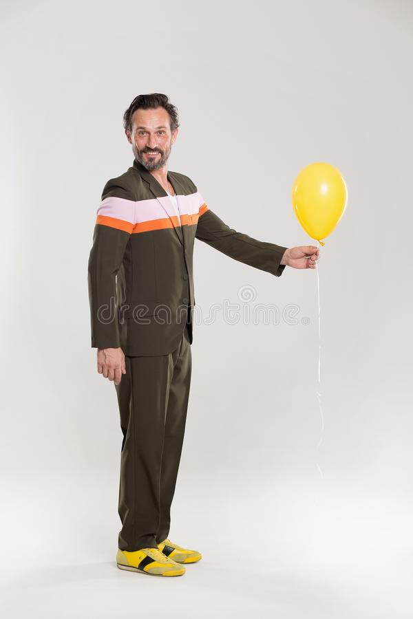 Happy man with yellow balloon. Handsome guy in funny suit. Holding yelloow balloon royalty free stock image