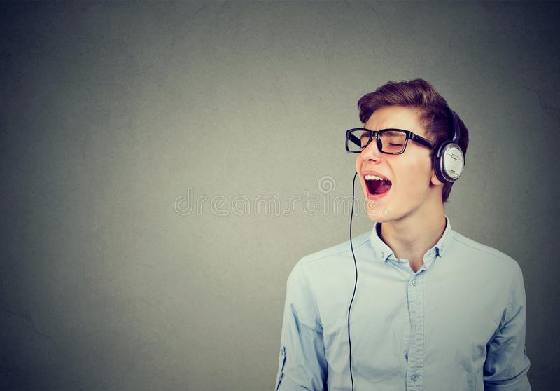 Handsome guy with headphones in blue shirt listening to music and singing royalty free stock photo