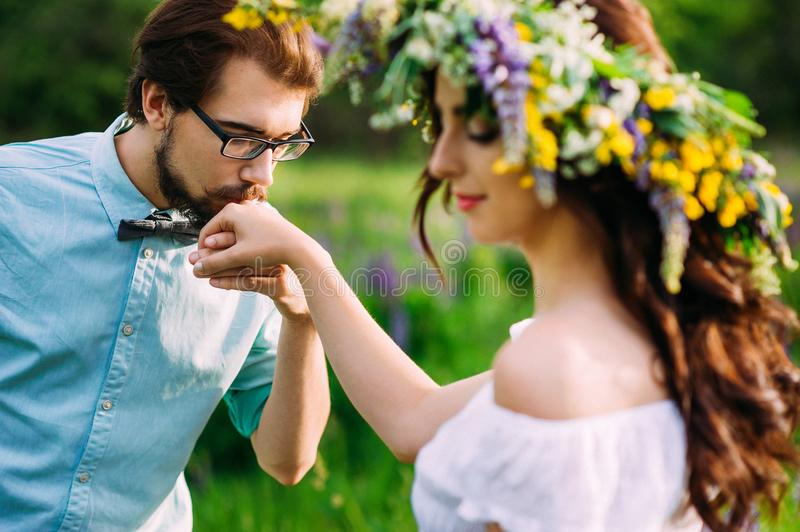 Handsome guy kiss a womans hand. Handsome guy with a beard in a blue denim shirt gentle kiss a womans hand royalty free stock images