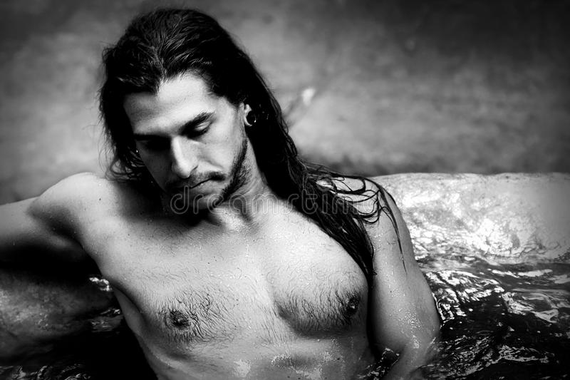 A handsome guy with long hair and piercings on waterfalls in a rain forest. Tarzan concept. Black and white photo. royalty free stock photography
