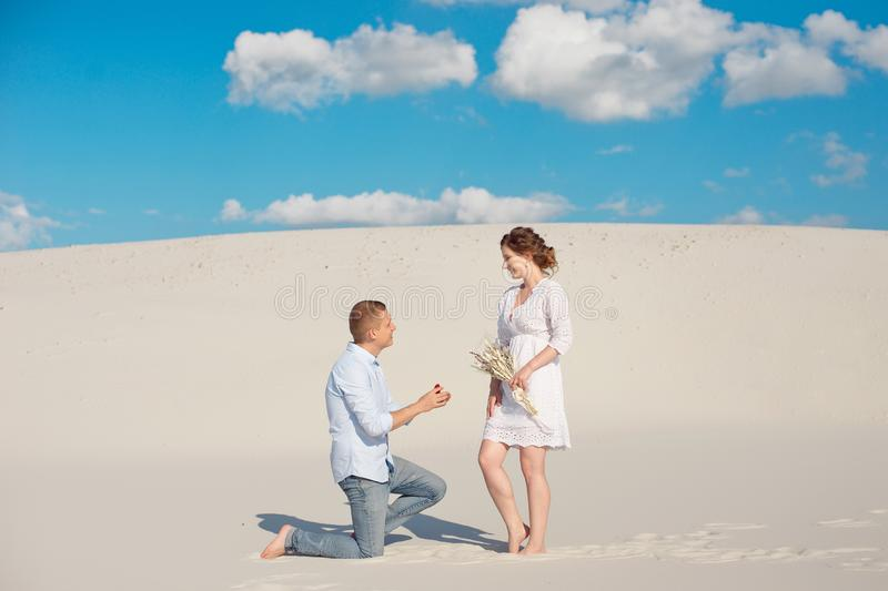 Handsome guy makes the girl a proposal for marriage, bending his knee, standing on the sand in the desert. Happy moments royalty free stock photo