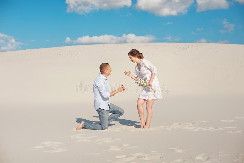 Handsome guy makes the girl a proposal for marriage, bending his knee, standing on the sand in the desert. Happy moments stock photo