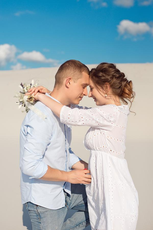 Handsome guy makes the girl a proposal for marriage, bending his knee, standing on the sand in the desert. Happy moments stock photography