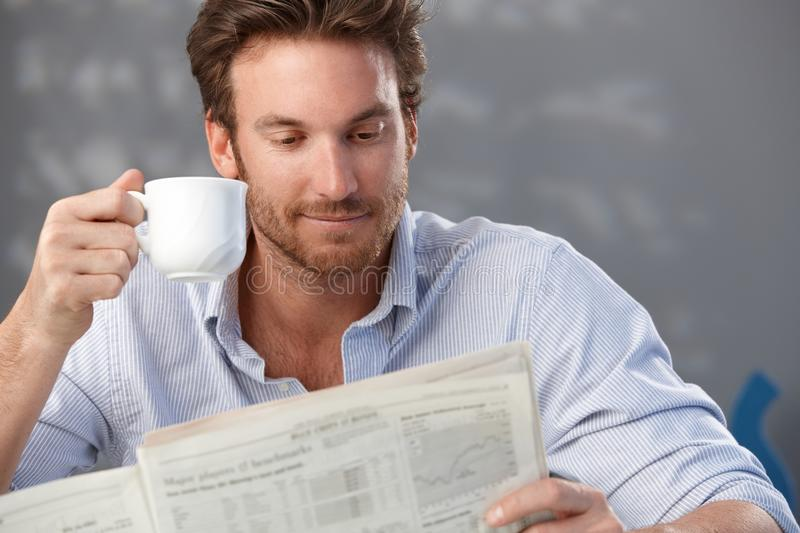 Handsome guy with newspaper. Morning portrait of handsome guy reading newspaper and holding coffee cup stock images