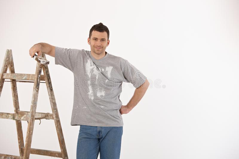 Handsome guy with paint brush and ladder. Portrait of handsome guy with paint brush and ladder, looking at camera, smiling royalty free stock photo
