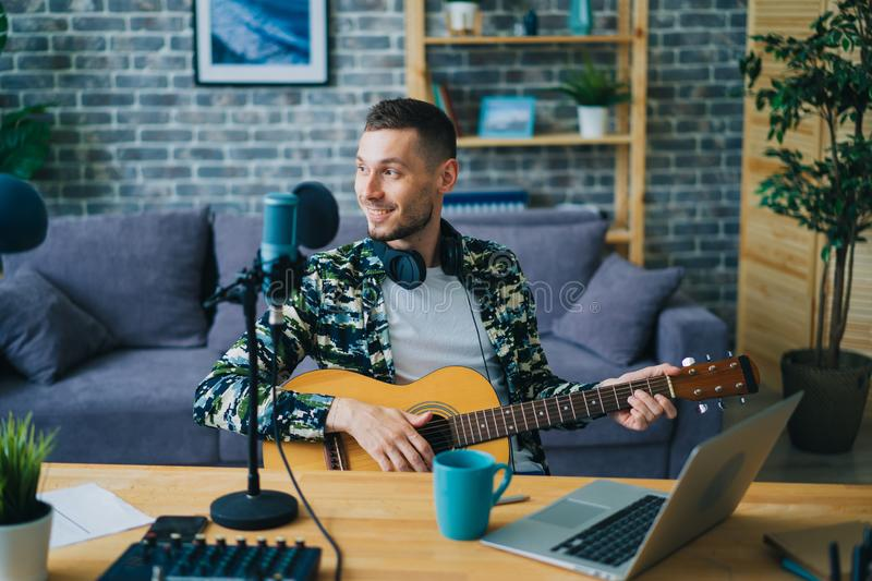 Handsome guy playing the guitar recording audio in studio using microphone stock photo