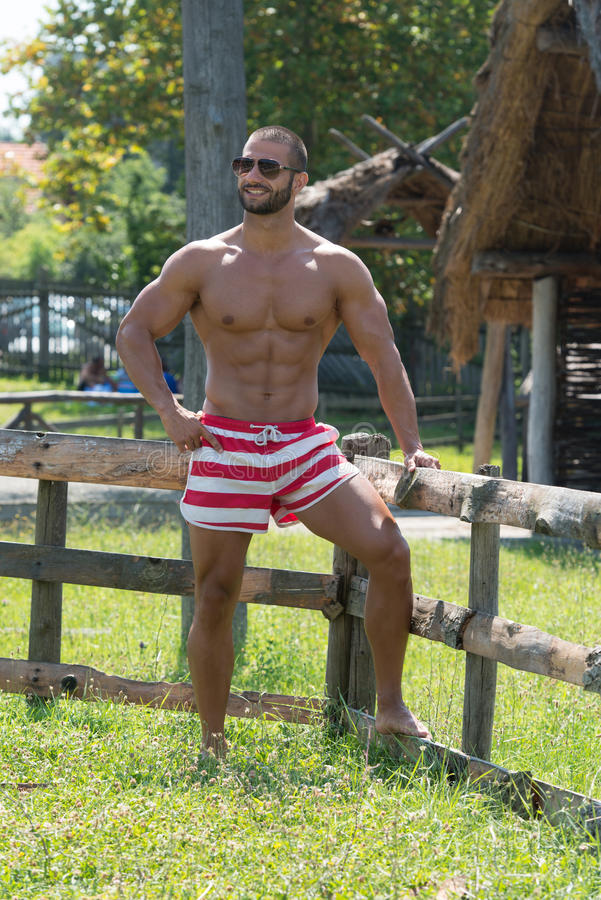 Handsome Guy Resting Outdoors While Enjoying Nature. Smiling Athlete With Naked Torso Resting Outdoors royalty free stock images