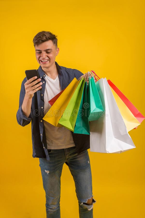 Handsome guy with shopping bags is using a mobile phone and smiling. Portrait of a smiling man holding shopping bag over yellow ba stock image