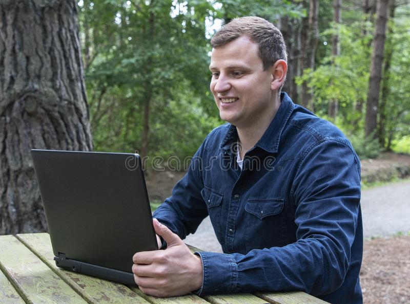 Man typing on a computer in the fresh air in the forest stock photos