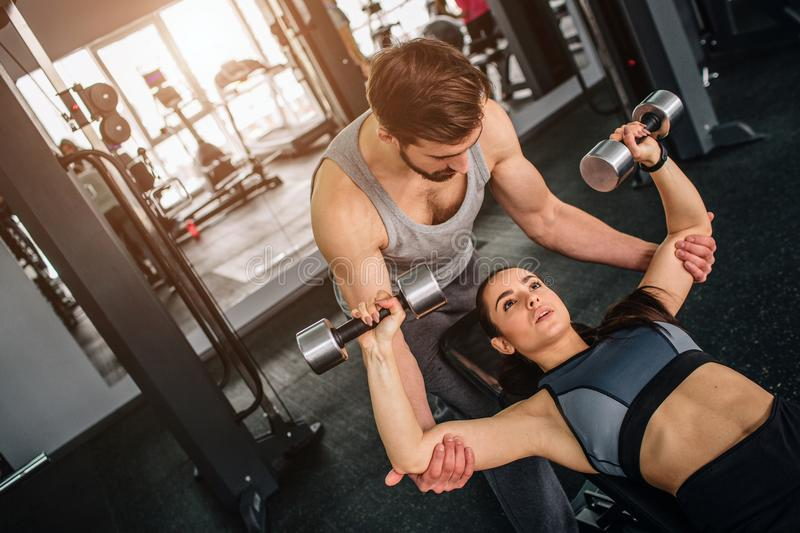 Handsome guy standing near his girlfriend and helping her to do exersices with a dumbbell. He is supporting her to make stock images