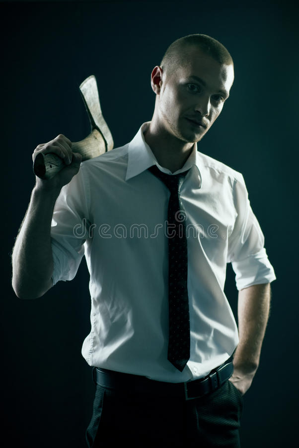 Handsome guy in studio with axe. Handsome guy in studio moody style stock photo
