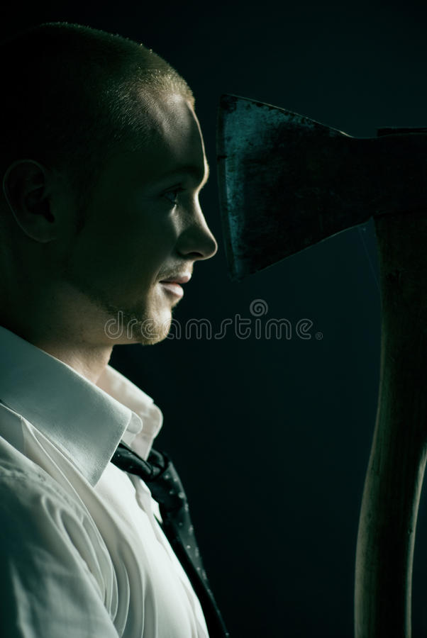 Handsome guy in studio with axe. Handsome guy in studio moody style royalty free stock photos