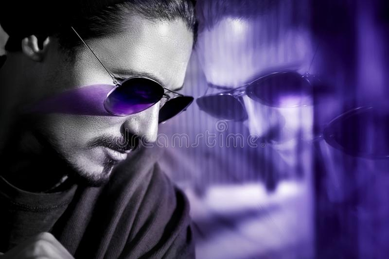 Handsome guy in sunglasses with reflection. Fashionable ultraviolet artistic image. Composite image with black and white. stock image