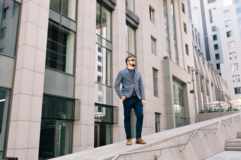Handsome guy in sunglasses is standing on office building background. He wears gray jacket, jeans, brown shoes. He keeps stock images